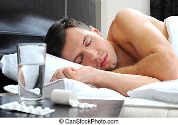 Sleeping - Man sleeping - pills on bed table. Headache