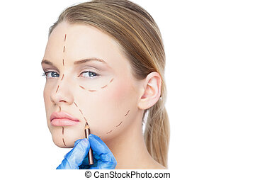 Surgeon drawing dotted lines on unsmiling patient before...