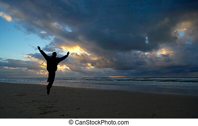 Joy - A person jumping for joy during sunset