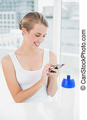 Happy blond woman sending a text message - Happy blond woman...