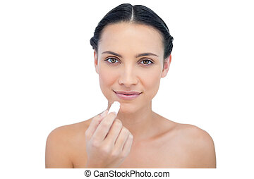 Natural model using lip balm on white background