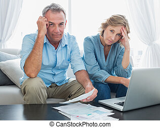 Anxious couple paying their bills online with laptop