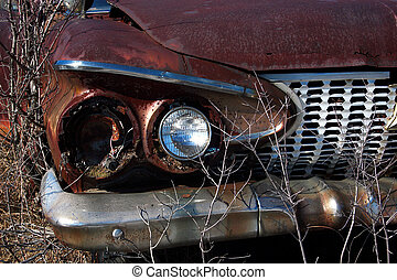 Rusty Car - Very rusted car wasting away in a junkyard
