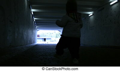a small child in tunnel - a small child walking in the...