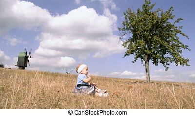 a small girl outdoors - a small girl sitting and clapping...