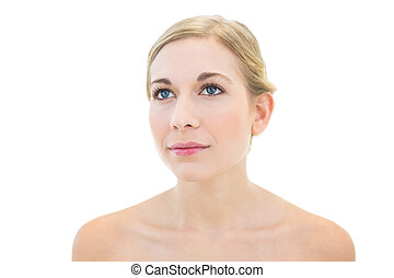 Pensive young blonde woman looking away on white background