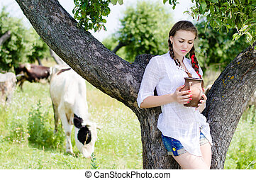 Young happy woman drinking fresh milk near cows in countryside