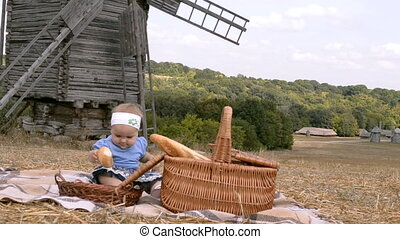 a small girl on picnic - a small girl eating bread on...