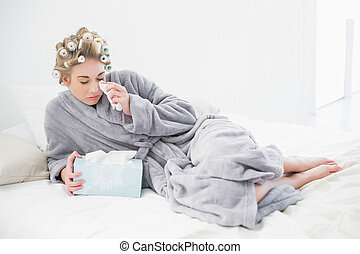 Sad blonde woman in hair curlers crying and using tissues in...