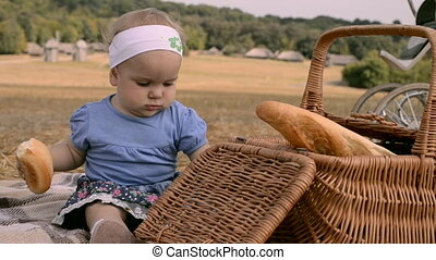a small girl outdoors - a small girl eating bread on...