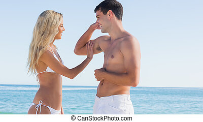 Man showing off muscles to pretty blonde at the beach