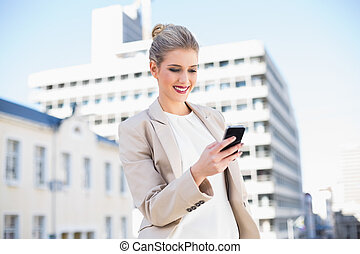 Cheerful attractive businesswoman sending a text message...