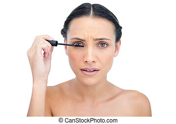 Annoyed young brunette applying mascara on white background