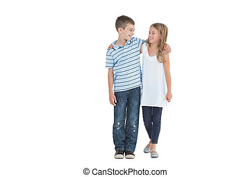 Smiling young brother and sister holding each other