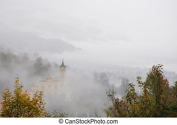 Church on the mountain with fog in autumn