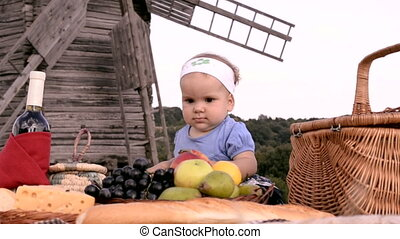 a small girl on countryside picnic - a small girl sitting on...