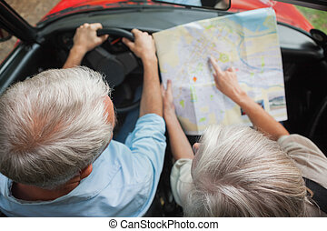Overhead view of mature couple on holidays reading map in...