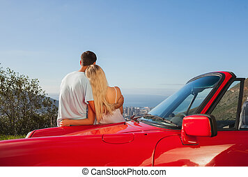 Rear view of couple hugging and admiring panorama on a sunny...
