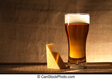 Beer And Cheese - Glass of freshness beer with foam near...