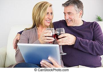 Happy couple toasting with wine sitting on a sofa - Happy...