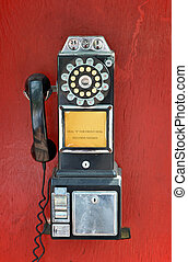 Payphone - An old fashioned pay phone against a red...