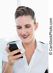 Close up view on smiling businesswoman using smartphone in...