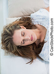 Peaceful woman sleeping in cosy bed