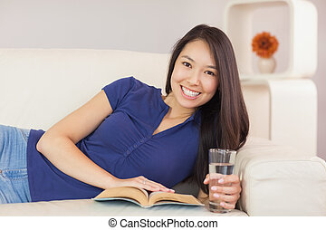 Beautiful asian girl lying on the sofa reading a novel and...
