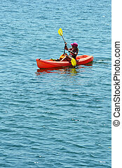 Kayaker - A lone kayaker rowing out on the ocean