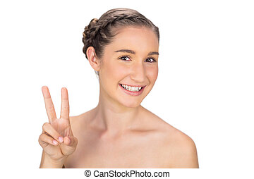 Smiling woman making peace and love gesture on white...