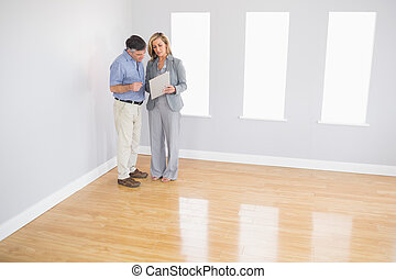 Serious blonde realtor showing an empty room and some...