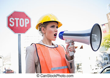 Businesswoman wearing builders clothes shouting in megaphone...