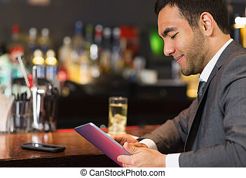 Close up of businessman sitting at bar and reading drinks...