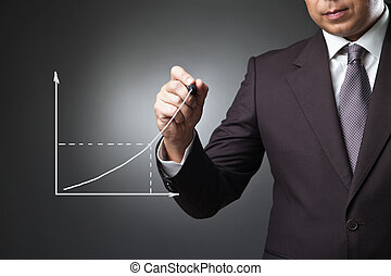 Business man drawing a growing graph on the screen over dark...
