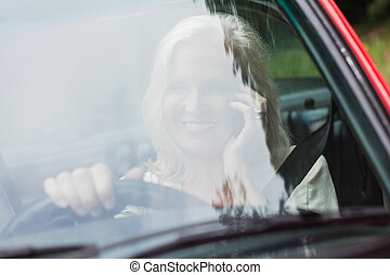 Cheerful mature woman on the phone driving red cabriolet on...