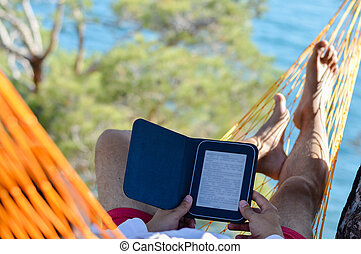 Man resting in hammock on seashore and reading ebook - Man...