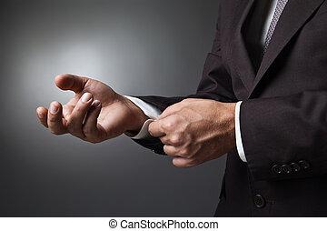 Close-up of elegance man hands with cufflink over dark...