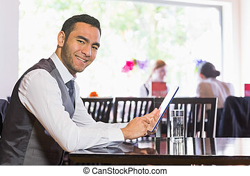 Happy businessman using tablet and smiling at camera in a...