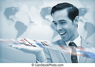 Delighted businessman looking at a picture stream on map...