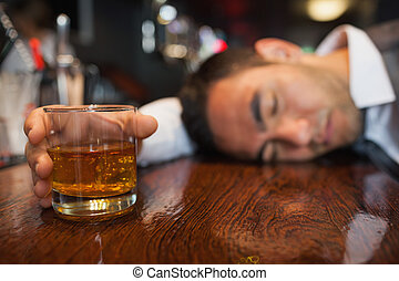 Drunk businessman with whiskey in his hand lying on a counter