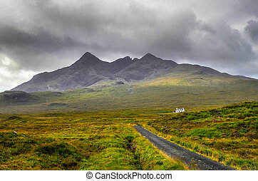 Cuillin Hills mountains with lonely house and road,...