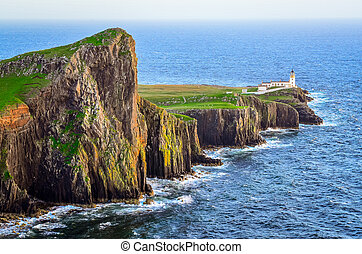 View of Neist Point lighthouse and rocky ocean coastline,...