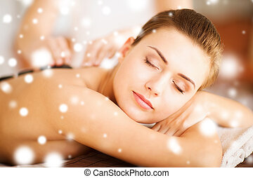 woman in spa with hot stones - health and beauty concept -...