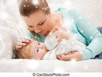 mother and adorable baby with feeding-bottle - family,...