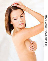 woman checking breast for signs of cancer - health,...