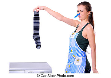 Washing - A housewife holding a male sock and her nose next...