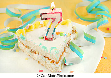 slice of seventh birthday cake with lit candle, confetti,...