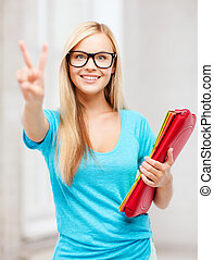 smiling student with folders showing victory sign -...