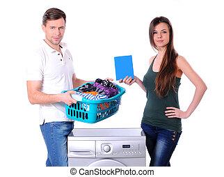 Washing - beautiful young couple with a washing machine