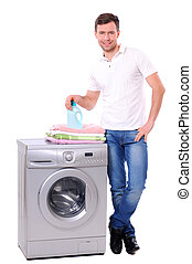 Washing - young male next to a washing machine isolated...